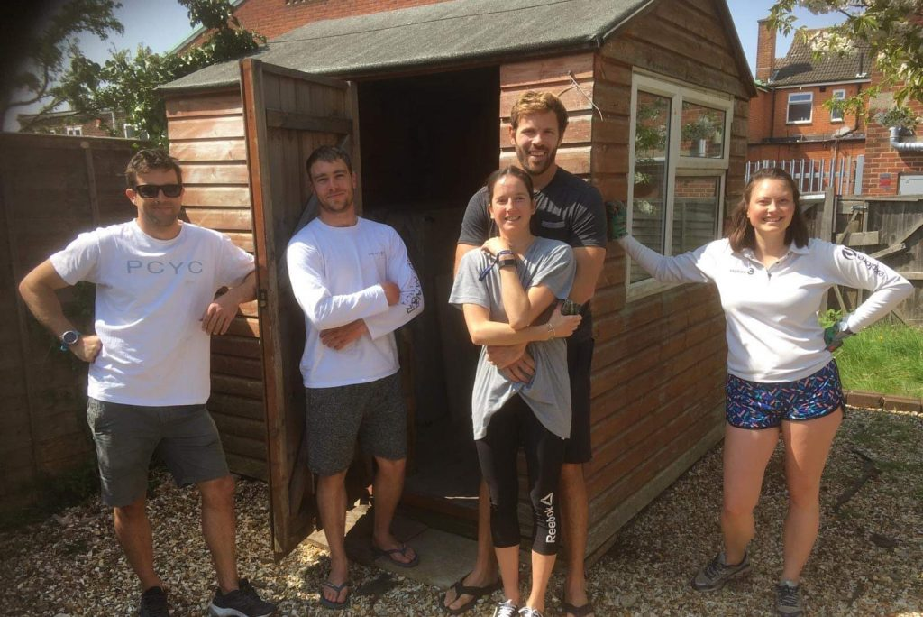 Housemates standing in front of shed