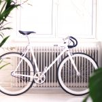 Bicycle in front of radiator in a room with plants